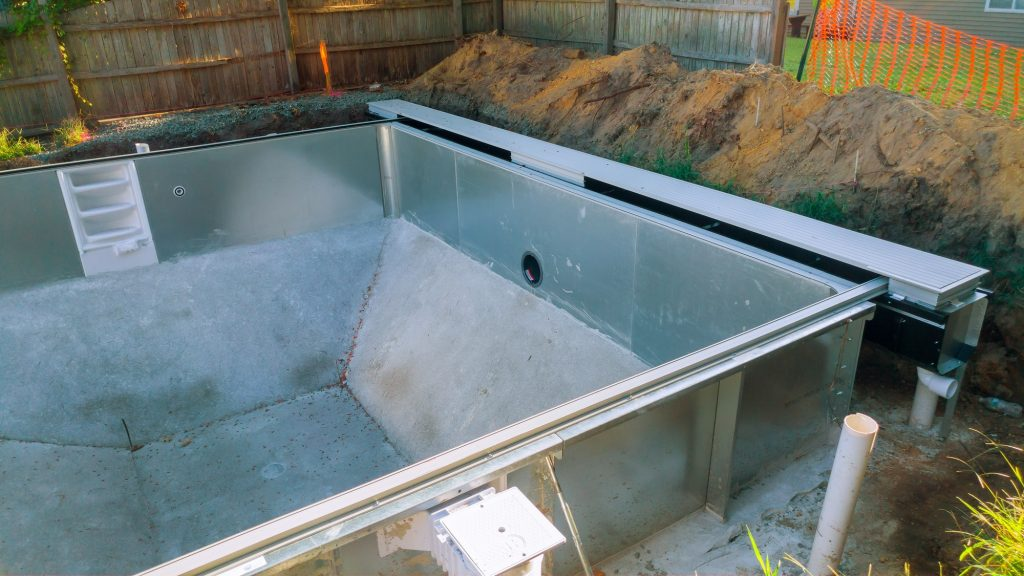 Installation pool in the ground at house backyard. Construction of the family house.